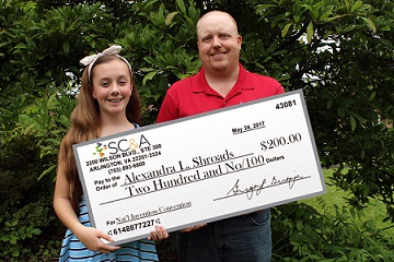 image of Alexandra Shroads receiving donation check